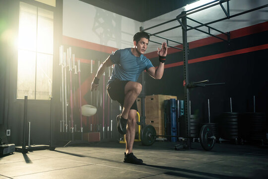 Caucasian young man doing cardio exercise by high knees pose in gym.