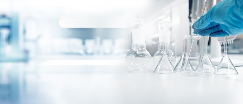hand of scientist with test tube and flask in medical chemistry lab banner background.