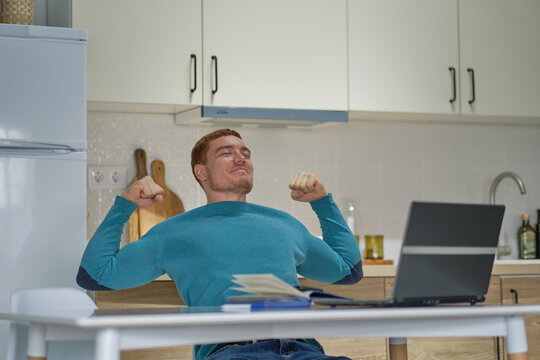 Happy excited man using laptop and raising his arms up to celebrate success at kitchen. success without leaving home, the new norm.