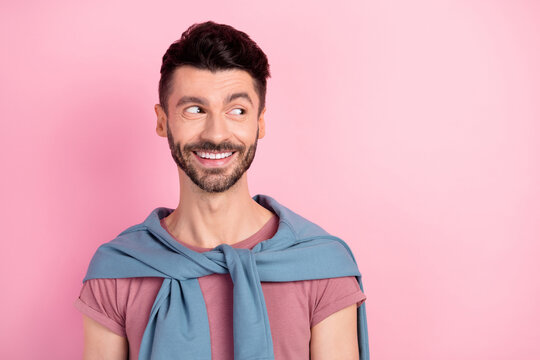 Photo of dreamy charming young happy man look empty space good mood isolated on pink color background