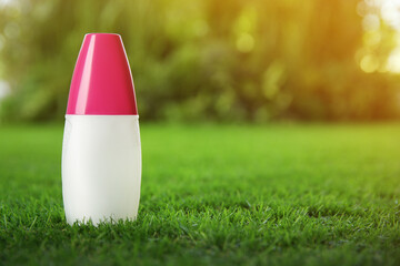 Bottle of insect repellent spray on green grass. Space for text