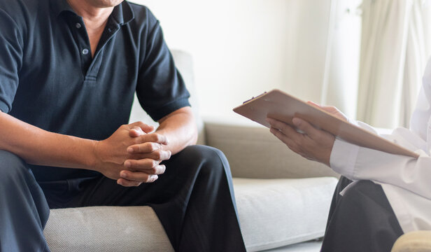 Doctor physician consulting with male patients in hospital exam room. Men's health concept