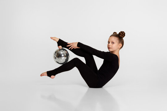 young gymnast in black sportswear doing an exercise with mirror ball on white studio background