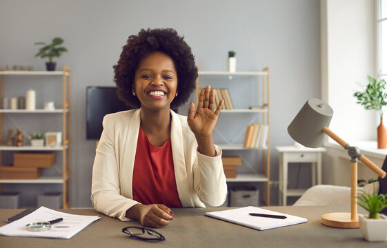Friendly african american business woman waving in front of webcam welcoming online conference attendees. Smiling female company employees enjoy virtual business communication and online negotiations.