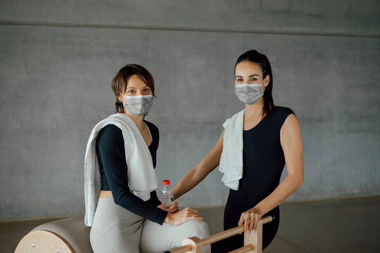 Portrait of two happy sportive women with towels and face masks, relaxing after training at gym, having a break, looking at camera and smiling. Happy to return to the gym after Covid-19 pandemic.