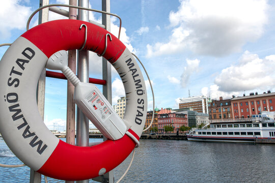 Pole with a lifebuoy at the sea entrance to the city of Malmo Sweden background of ship and buildings of the place