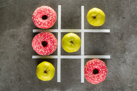 Healthy vs unhealthy food, green apples vs donuts in tic tac toe game