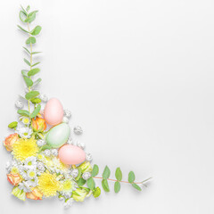 Creative layout composition of flowers and easter eggs on pastel background.