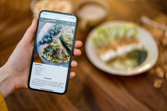 Digital recipe of healthy breakfast with pancake on the phone screen on wooden table top in kitchen with ready meal on background. Phone in the hand.