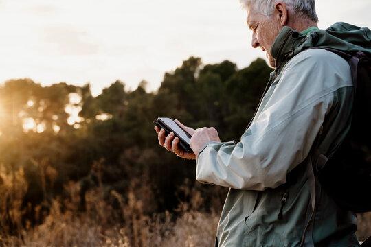 Senior man using smart phone during sunset