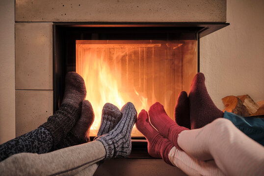 Family warming up feet in woolen socks by fireplace in living room