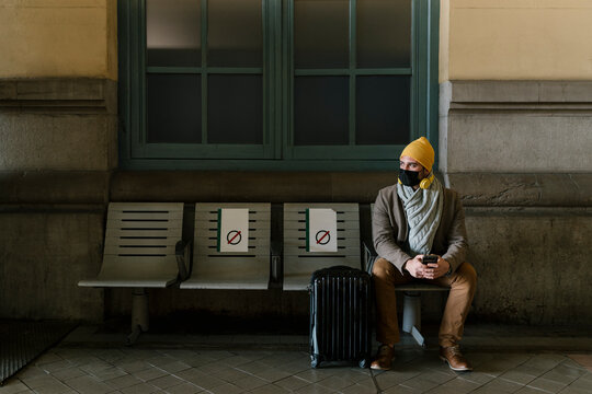Man wearing knit hat and protective face mask sitting with luggage on bench at station