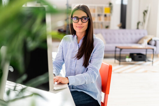 Female professional wearing eyeglasses using laptop while sitting by desk at office