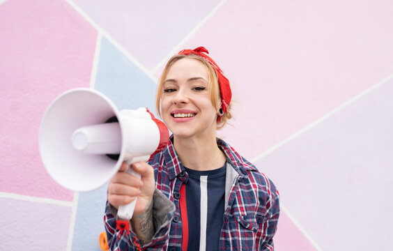 Smiling woman holding megaphone while standing against wall