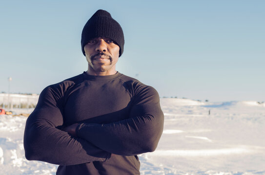 Muscular build sportsman wearing knit hat standing with arms crossed in snow during sunny day