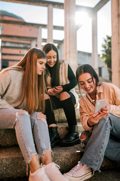 Smiling teenage girl showing mobile phone to friends while sitting on steps