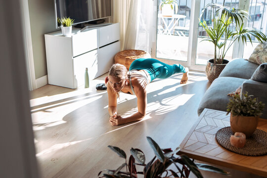 Woman practicing plank position while exercising on floor at home