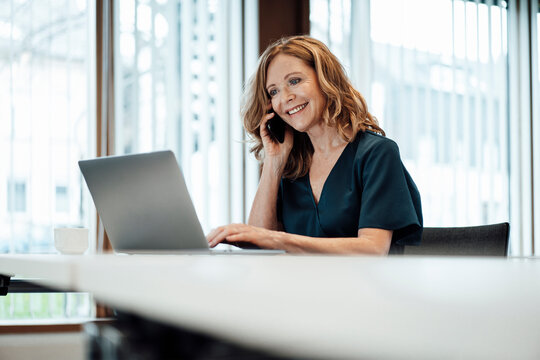 Smiling female entrepreneur working on laptop while talking over smart phone at board room