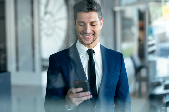 Smiling entrepreneur wearing suit using mobile phone while standing in office