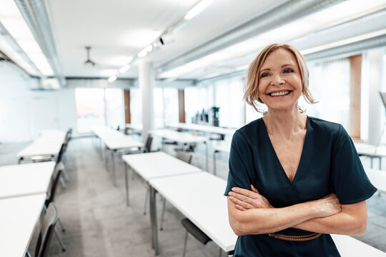 Female entrepreneur with arms crossed looking away in board room at office