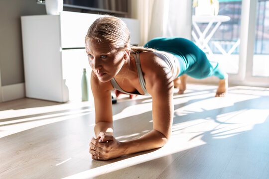 Woman practicing plank position while doing workout at home
