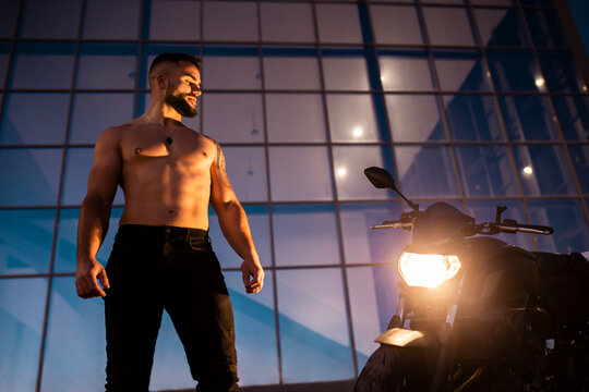 Shirtless handsome man staring motorcycle while standing against modern building