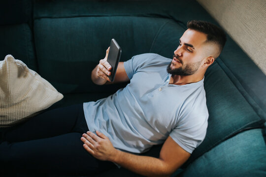 Handsome man using smart phone while lying on sofa at home