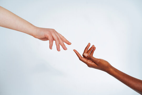 Friends stretching hands toward each other against white background