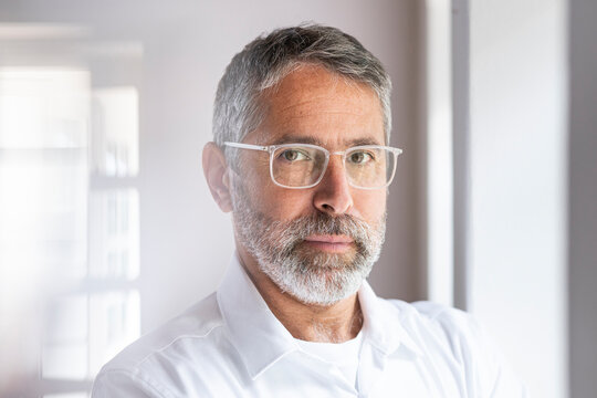 Confident businessman wearing eyeglasses staring while standing at home