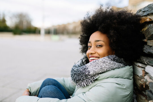 Smiling young woman in warm clothing while sitting outdoors