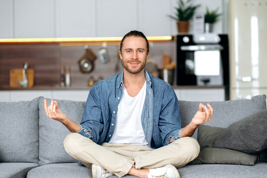 Modern carefree caucasian guy in a stylish casual clothes meditates while sitting in the lotus position on the sofa in the living room smiling, relaxing. Calmness and harmony concept