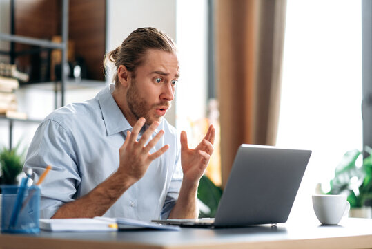 Shocked annoyed caucasian busy guy looking at a laptop in confusion, received unexpected news, failed a deal, shouts, gesturing with hands, sitting at the work desk at home office