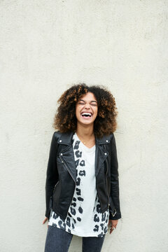 Laughing brunette with afro on textured concrete wall