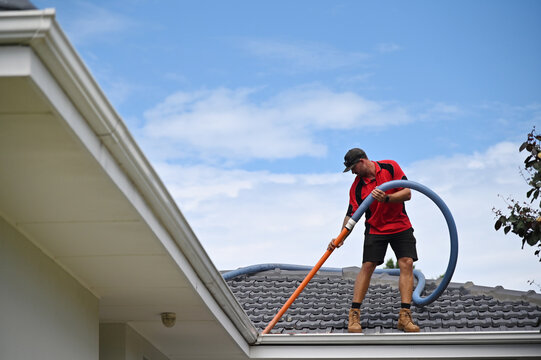Professional young Gutter cleaner cleaning gutters working on house roof.
