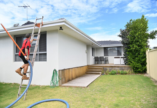 Professional young Gutter cleaner climbing on a ladder to clean gutters working on house roof