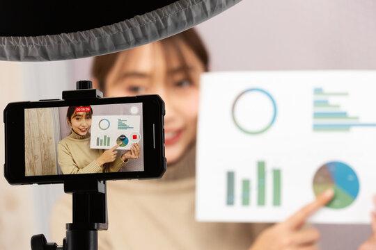 スマートフォンで動画を撮影する女性