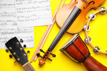 Different musical instruments and music notes on color background, closeup