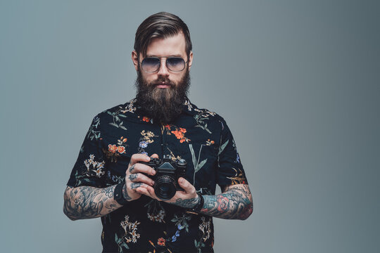 Successful hipster person with bearded face and modern coiffure posing in gray background holding photo camera.