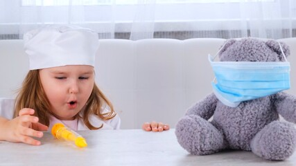 little girl plays a doctor, makes an injection. Happy child little doctor examines a teddy bear....