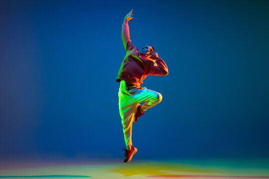 Young hip-hop dancer dancing isolated over blue background in neon light
