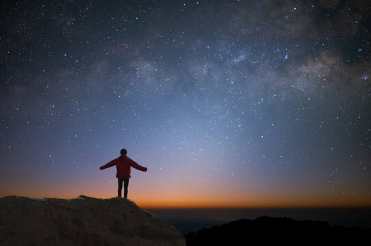 Silhouette of young traveler and backpacker watched the star and milky way alone on top of the mountain. He enjoyed traveling and was successful when he reached the summit.