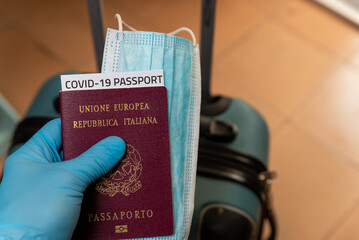 hand with latex gloves holding covid vaccine passport and face mask concept with luggage at...