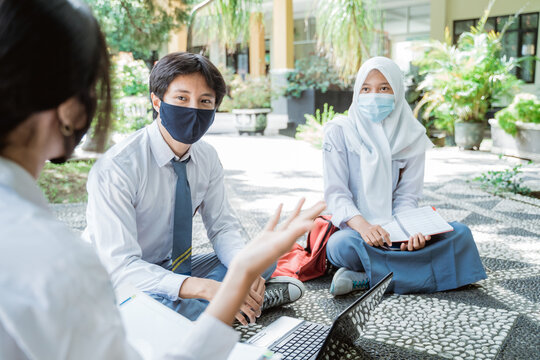 two high school children wearing masks watching their friend who is explaining during an outdoor group