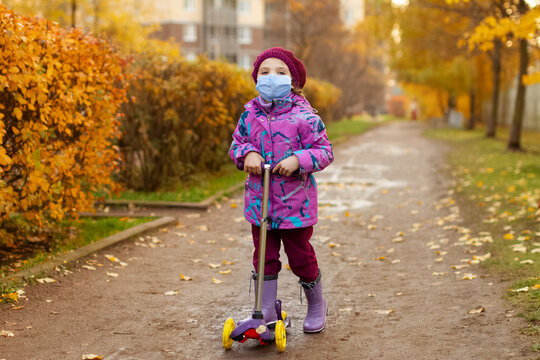 Girl of 3 years in purple clothes, protective mask with scooter in autumn on street