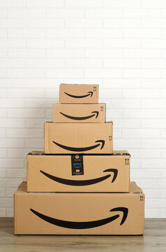Group of Amazon cardboard boxes on white brick wall background. Bergamo, Italy, 5 march 2021.