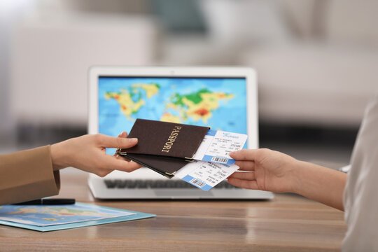 Travel agent giving tickets and passports to client in office, closeup