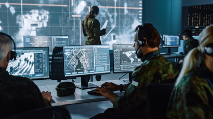 Obraz Military Surveillance Officer Working on a City Tracking Operation in a Central Office Hub for Cyber Control and Monitoring for Managing National Security, Technology and Army Communications. - fototapety do salonu