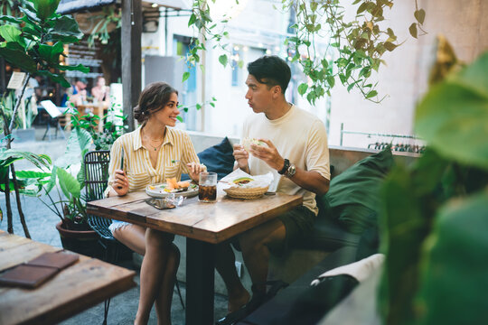 Young couple having lunch and chatting in cafe