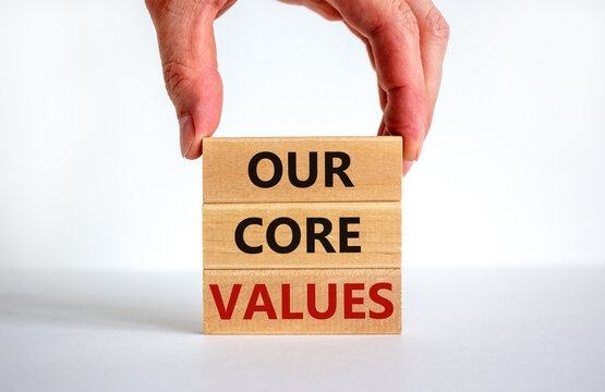 Our core values symbol. Concept words 'Our core values' on wooden blocks on a beautiful white background, businessman hand. Business and our core values concept. Copy space.