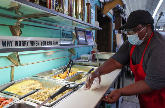A worker cleans the counters along the buffet line at Pap's Place catfish restaurant in Ackerman, Mississippi